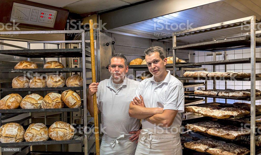 Bakers em fazer pão de padaria, - fotografia de stock
