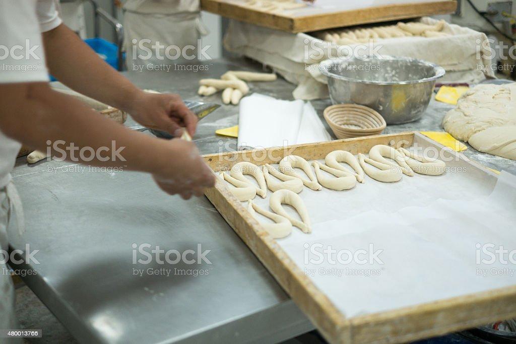 Bakers der frische Teig mit Brezeln auf Tisch – Foto