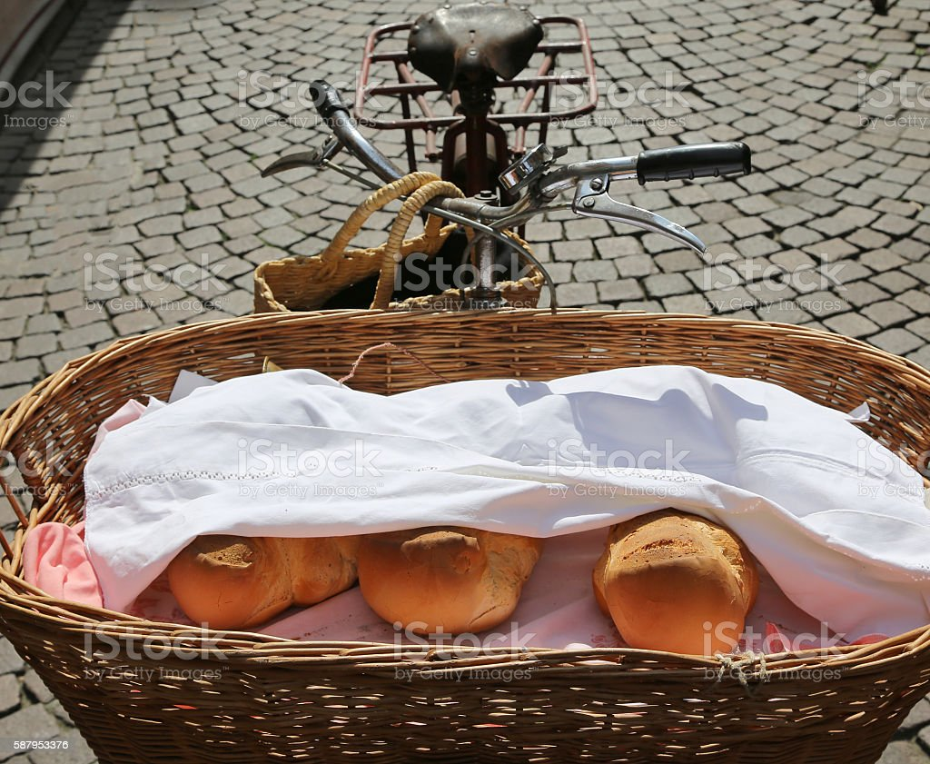 Baker's old bicycle with basket with  pieces of fragrant bread stock photo
