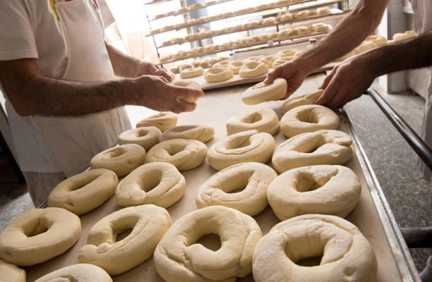 Bakers preparing dough for bagels - foto stock