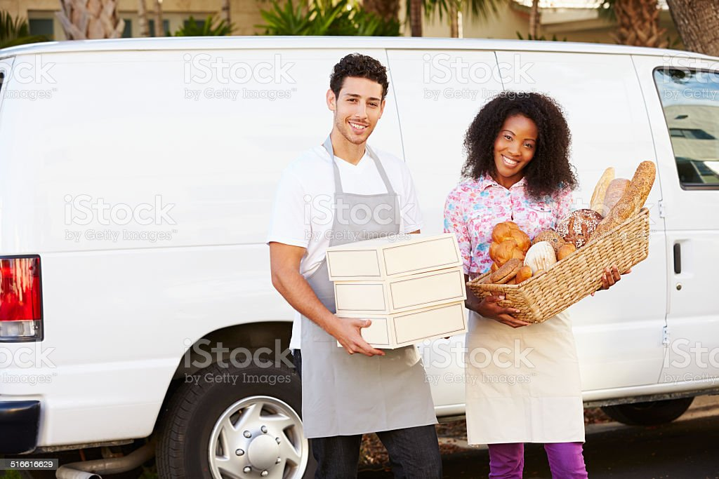 Bakers Unloading Bread And Cakes From Van stock photo