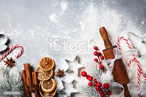 istock Bakery background for cooking christmas baking with rolling pin, scattered flour and spices decorated with fir tree top view. 1050300200