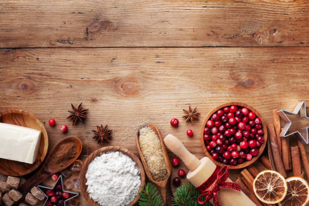 bakery background with ingredients for cooking christmas baking. flour, brown sugar, butter, cranberry and spices on wooden table top view. - christmas cooking imagens e fotografias de stock