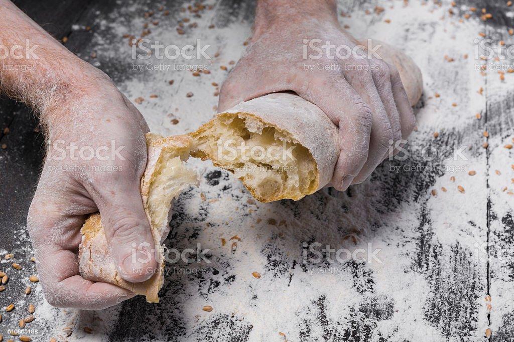 Bakery concept background. Hands breaking bread loaf – Foto