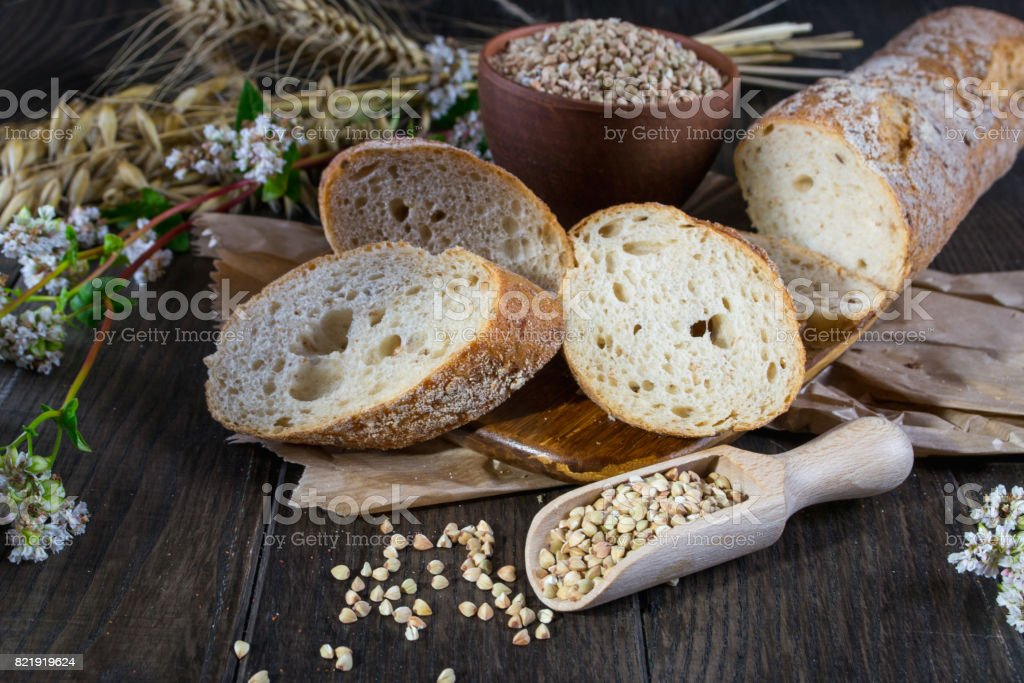 Bakery concept. Buckwheat bread, French baguette and stalks of whea, oats, buckwheat – zdjęcie