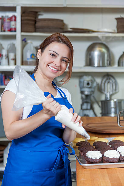 bakery decorating cupcakes in a commercial bakery stock photo - Woman Decorating Cupcakes