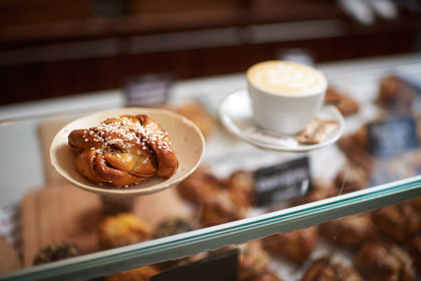 Bakery goods Close up view of baked pastry item and cup of coffee inside a bakery. sweet bun stock pictures, royalty-free photos & images