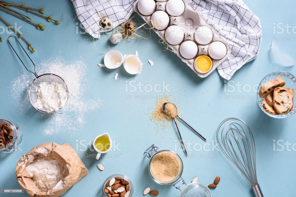 Bakery ingredients - flour, eggs, butter, sugar, yolk, almond nuts on blue table. Sweet pastry baking.