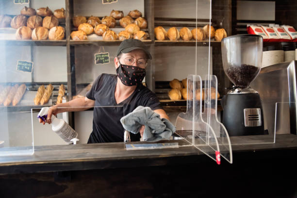 Bakery owner wiping down surfaces wearing mask. stock photo