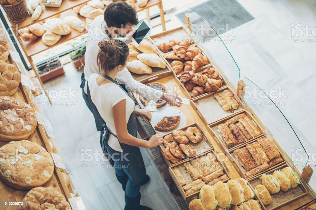 Bakery owners arranging the display in the bakery stock photo