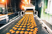Bakery production line with sweet cookies on conveyor belt in confectionery factory workshop, food production manufacturing.