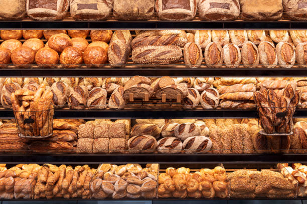 Bakery shelf with many types of bread. Tasty german bread loaves on the shelves_ Delicious loaves of bread in a german baker shop. Different types of bread loaves on bakery shelves. bread stock pictures, royalty-free photos & images