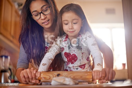 Shot of a mother and her little daughter baking together at home
