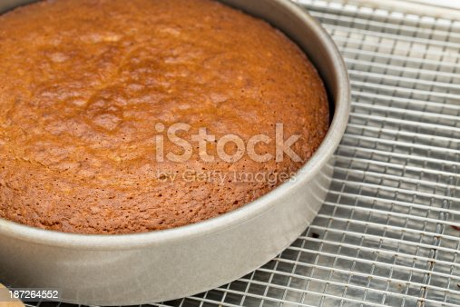 A high angle close up of a freshly baked banana cake sitting on a metal cooling rack