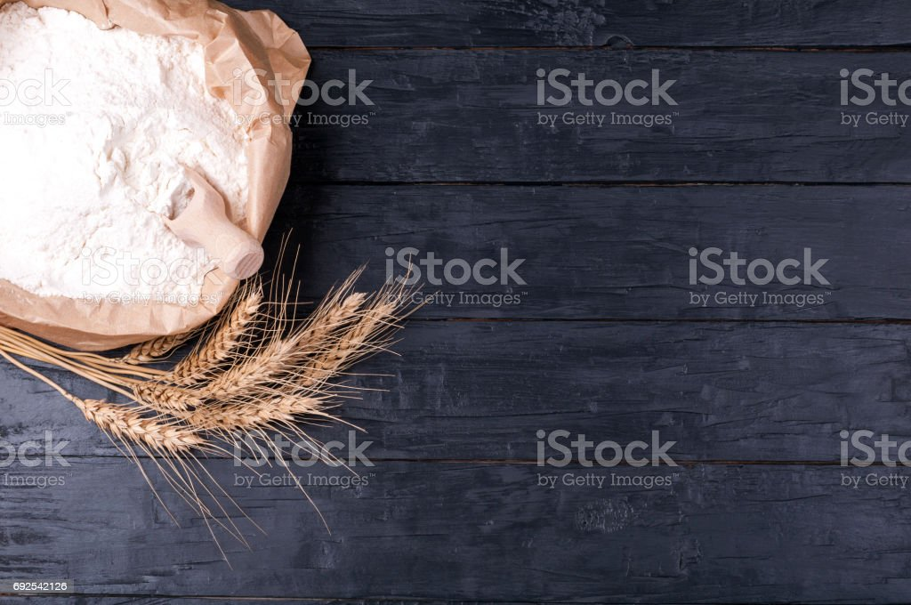 Baking background. Flour in paper bag and wheat on dark wooden table. Ingredients for cooking.  Top view. Copy space stock photo