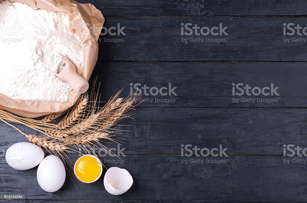 Baking background. Flour in paper bag, wheat and eggs stock photo