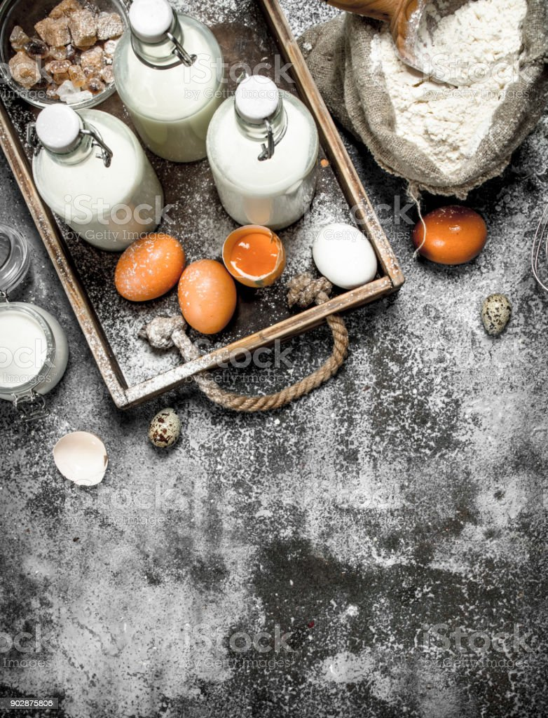 Baking background. Flour with fresh milk in bottles, sour cream and eggs. stock photo