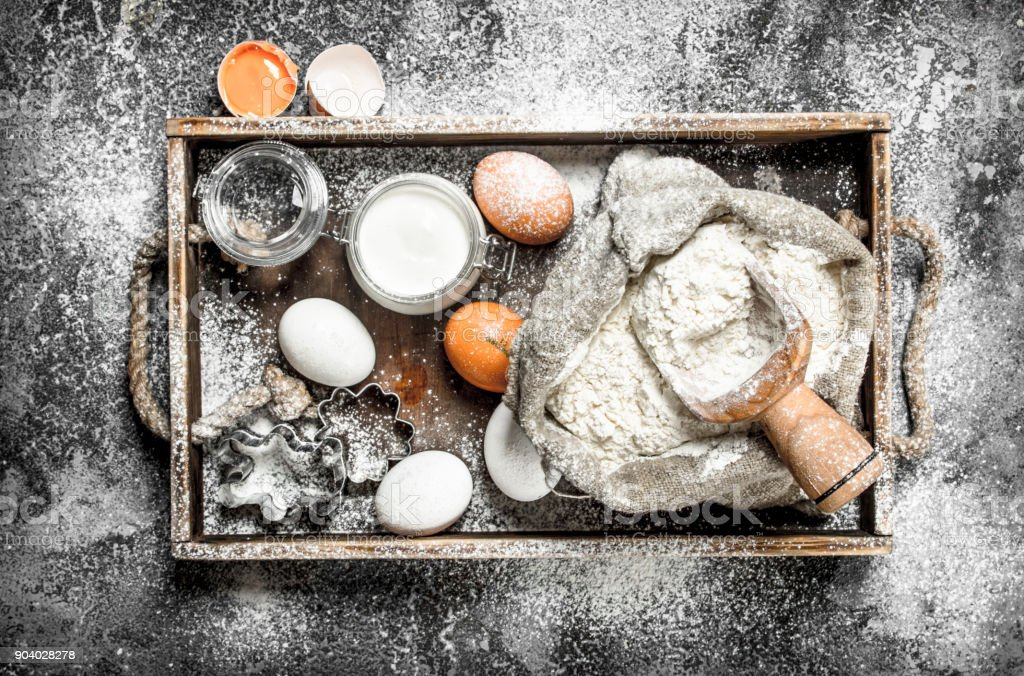 Baking background. Ingredients for dough in a wooden tray. stock photo