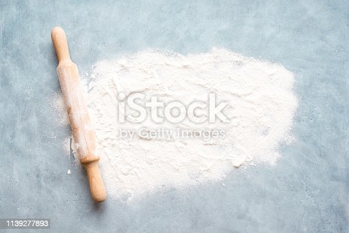 Flour and rolling pin on blue background, top view, copy space. Homemade baking concept, space for text.