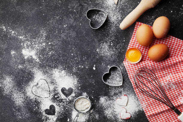 Baking background with flour, rolling pin, eggs, and heart shape. stock photo