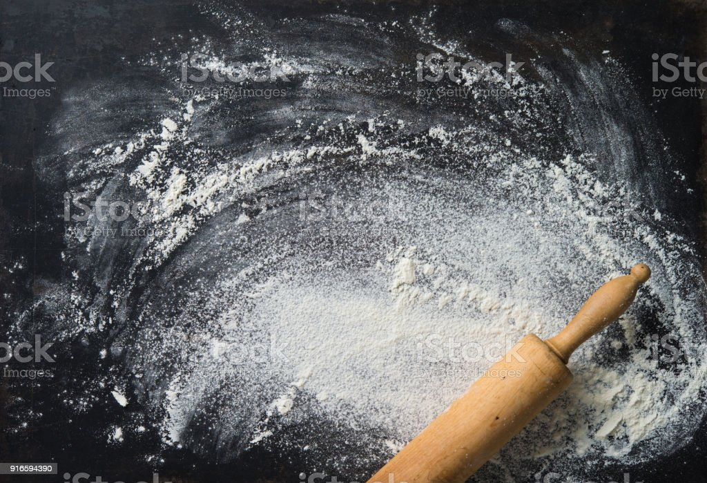 Baking background with the rolling pin and flour. On the dark table stock photo