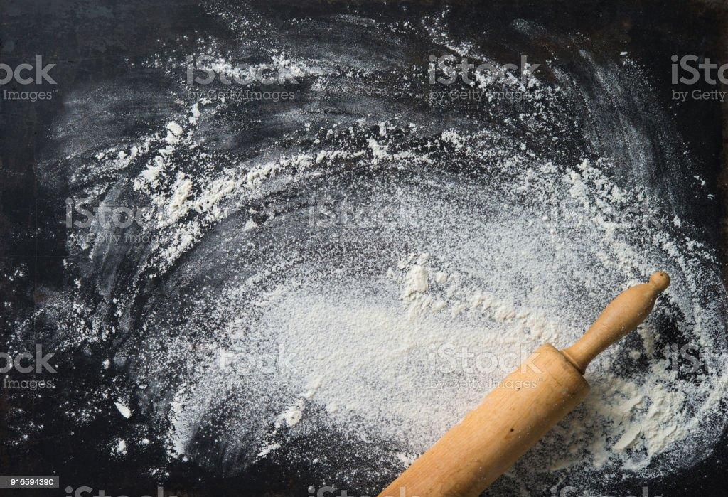Hintergrund das Nudelholz mit Mehl backen. Auf dem dunklen Tisch – Foto