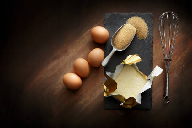 Baking: Butter, Eggs, Sugar and Whisk Still Life stock photo