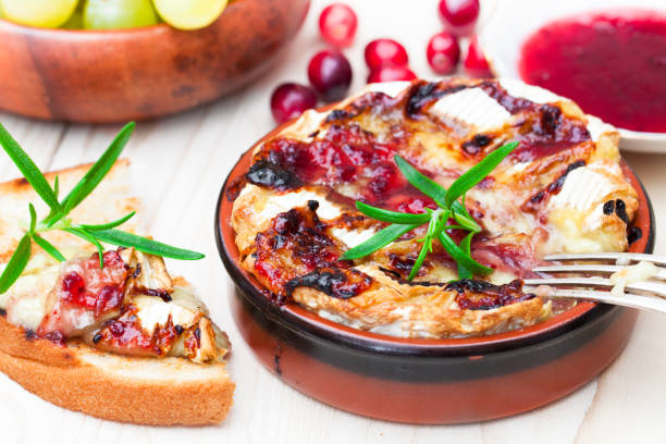 baking  camembert with cranberry sauce and rosemary served with toasted bread and grapes - baked brie stock photos and pictures