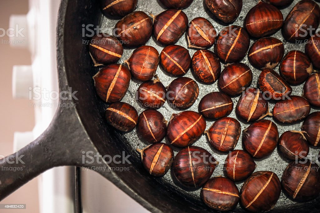 Baking chestnuts in cast iron pan stock photo