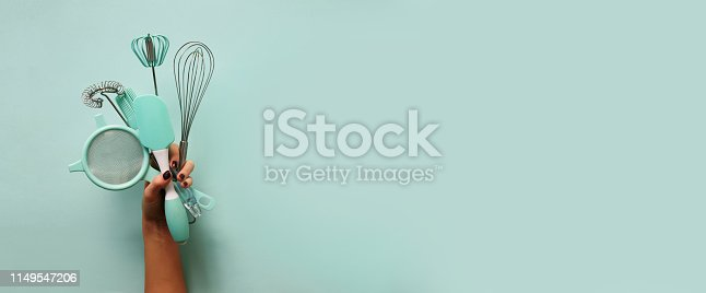 Baking flat lay. Female hands holding kitchen tools, sieve, rolling pin, spatula and bruch on pastel blue background. Banner with copy space. Top view.