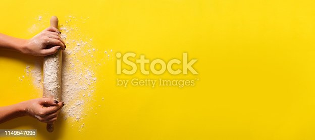 Baking flat lay with rolling pin, flour on yellow paper background. Bake menu, recipe, homemade pastry concept. Top view. Banner with copy space for your text.