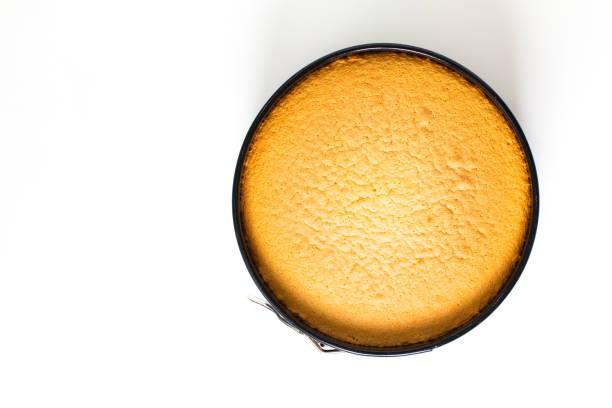 backfutterkonzept frisch gebackener hausgemachter schwammkuchen in kuchenpfanne auf weißem hintergrund mit kopierraum - biskuitboden stock-fotos und bilder