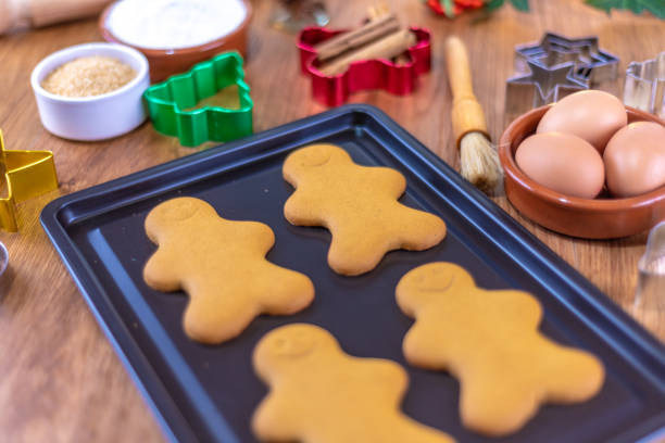 baking gingerbread characters at christmas on a baking tray - christmas stock photos and pictures