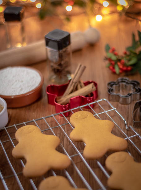 baking gingerbread characters at christmas - christmas stock photos and pictures