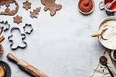 Baking gingerbread man Christmas cookies in kitchen. Cookie dough, with flour, rolling pin, cutter, cocoa powder and honey on kitchen counter for preparing gingerbread cookies for Christmas and new year.