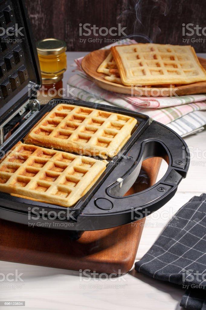 Baking homemade Belgian waffles in the waffle maker. stock photo