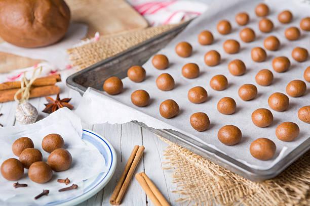 baking homemade pepernoten or kruidnoten for dutch holiday sinte - kruidnoten stockfoto's en -beelden