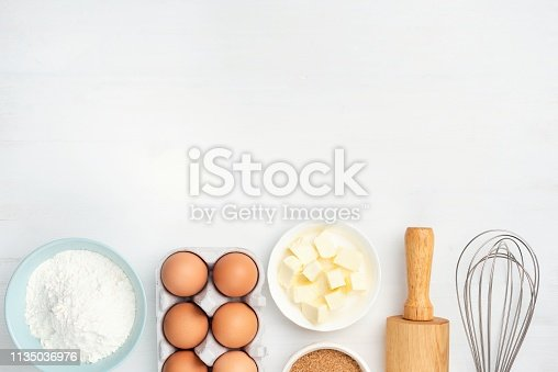 Baking ingredients and kitchen utensils on white background. Chicken eggs, butter, sugar, flour, rolling pin and whisker. Cooking, baking, pastry or cookie dough ingredients