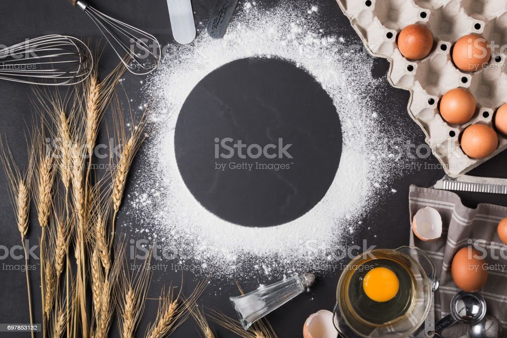 Baking ingredients: egg and flour on black board. stock photo