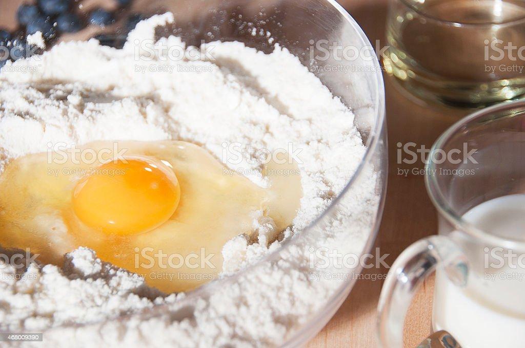 Baking ingredients, flour, egg, milk, oil and blueberries stock photo