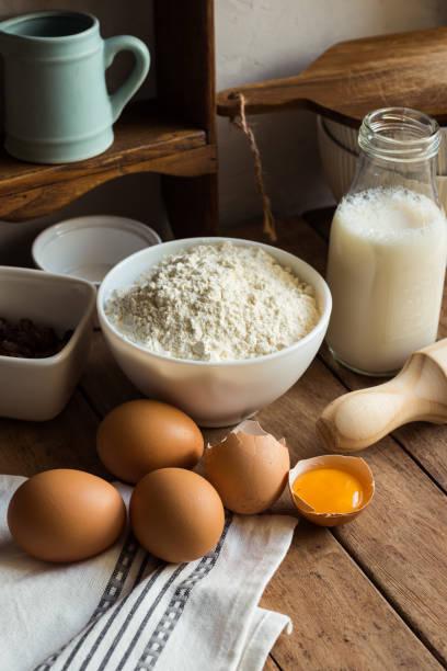 backen, zutaten mehl, eiern, offene eigelb, milch, nudelholz, schrank, rosinen, rustikale küche interieur, geschirr, geschirr - bett landhausstil stock-fotos und bilder