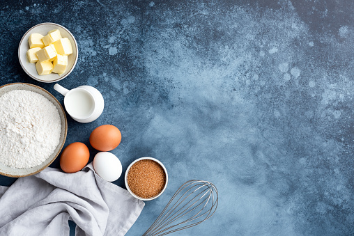 Baking ingredients flour eggs sugar milk and butter on a painted blue background. Top view copy space. Baking concept