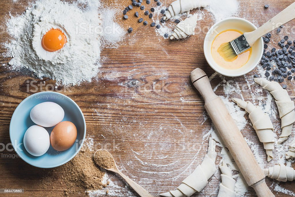 Baking ingredients for cooking croissants over wooden background, copy space royalty-free stock photo