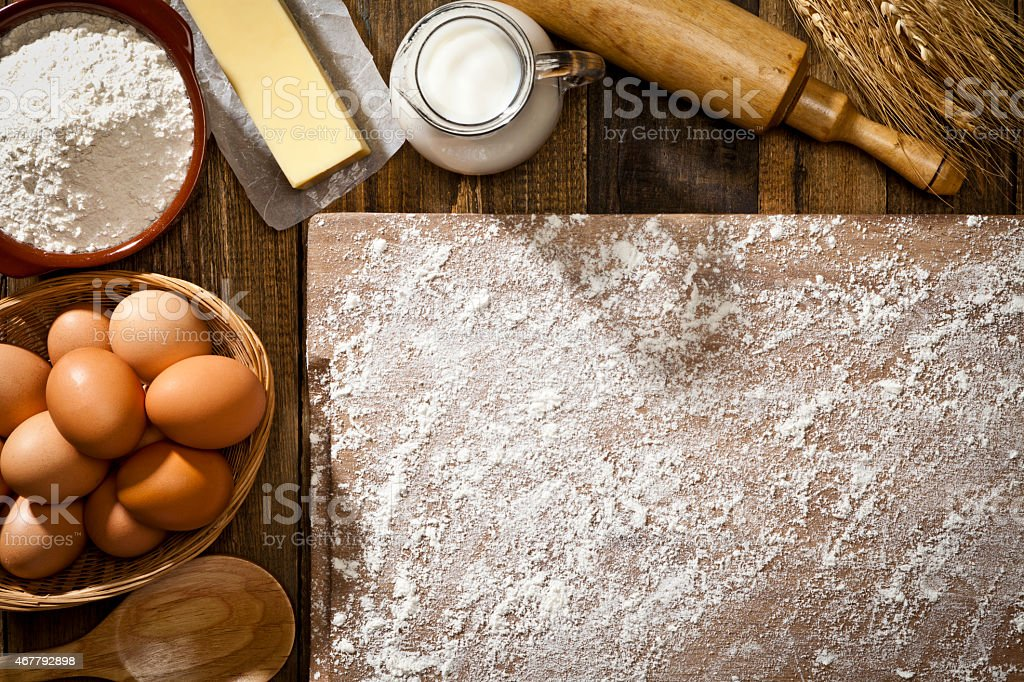 Baking ingredients in a half frame shape on wooden table stock photo
