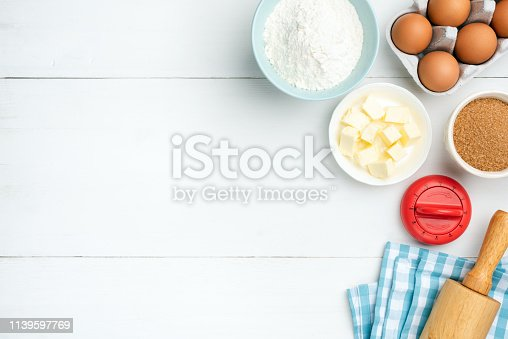 Baking ingredients on white background. Kitchen timer, rolling pin, textile, butter, eggs, sugar and flour. Copy space for text, recipe or menu