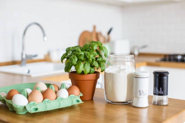 Backzutaten auf Holztisch, Pizzateig gelegt. Konzept der Zubereitung von Speisen. Weiße Küche im Hintergrund – Foto