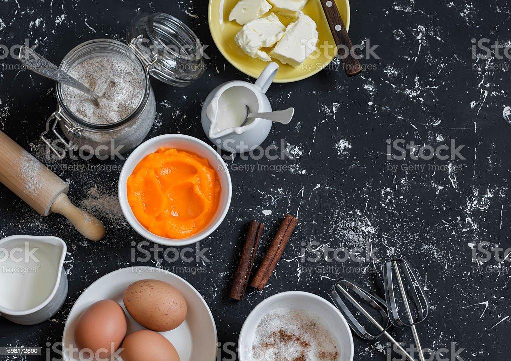 baking ingredients - pumpkin puree, butter, flour, eggs, cream, cinnamon stock photo