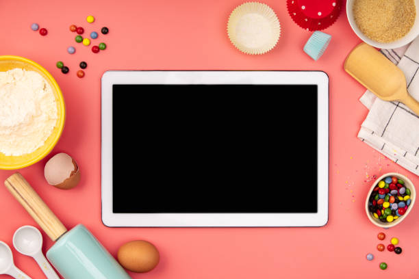 Baking ingredients with empty tablet on pink background, flat lay stock photo