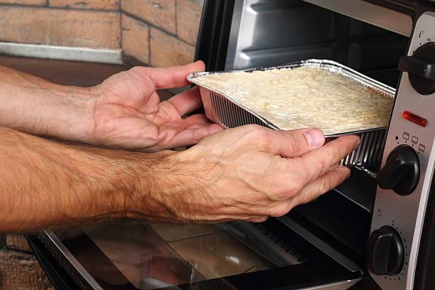 baking lasagne bolognese in disposable foil dish in oven - alufolie backofen stock-fotos und bilder