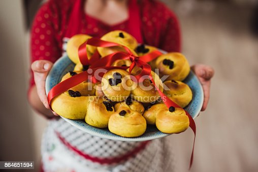 Baking Lucia saffron bun little girl showing tray